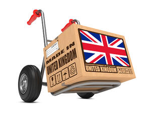 Cardboard Box with Flag of United Kingdom and Made in United Kingdom Slogan on Hand Truck White Background. Free Shipping Concept.